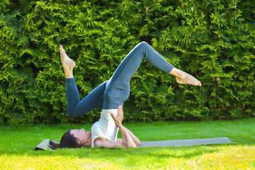 woman doing yoga on a green grass at summer day