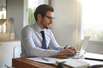 Attractive businessman typing on laptop in modern office