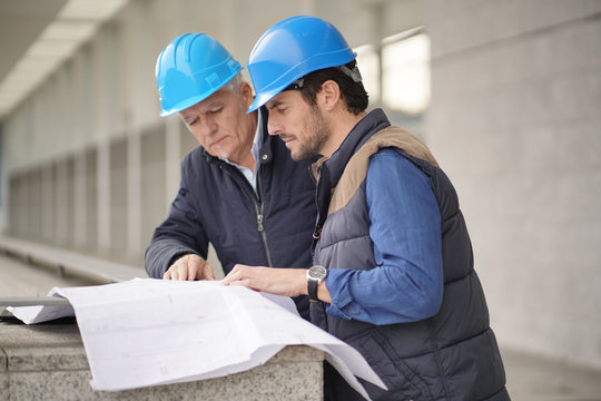 Workmen in hard hats consulting over blueprint on modern building sight