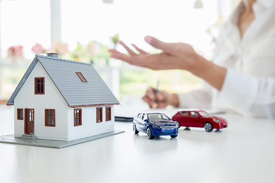 Car and House model with agent and customer discussing for contract to buy, get insurance or loan real estate or property background.