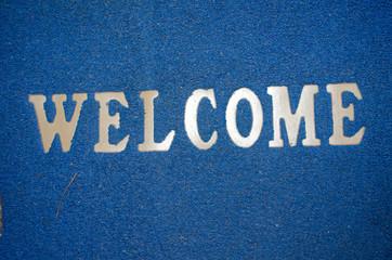 welcome inscription on blue background, carpet