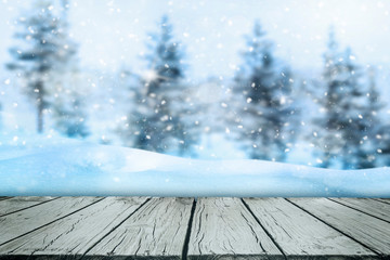 Wooden surface with snow and blur pine trees in background.