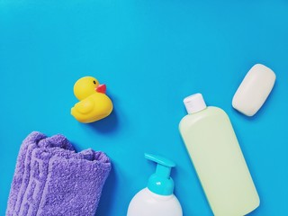 Flat lay baby natural baby bath products for skin and hair care. Shampoo, purple towel, liquid soap and rubber duck toy