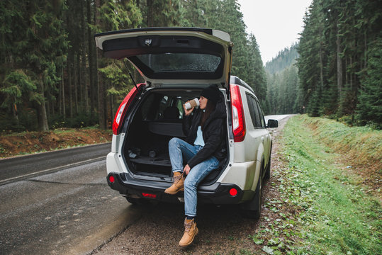 young pretty woman sitting in suv car trunk at road side drinking hot coffee at road side in mountain forest