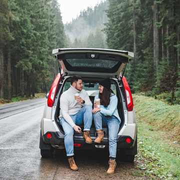 couple stop to drink hot tea. road trip concept. sitting in suv trunk at road side in mountains forest