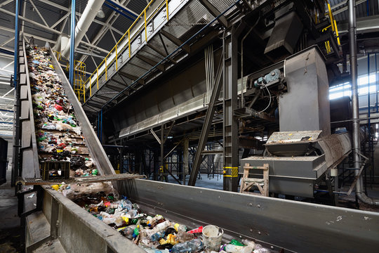 Conveyor belt at recycling plant transports garbage inside drum filter or rotating cylindrical sieve with trommel or screen for sorting pieces of garbage into various sizes fractions