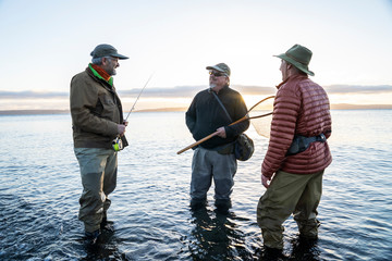 Two fly fisherman talk wtih their guide about new tecnhiques while fly fishing for searun coastal cutthroat trout at a beach on the north west coastline of the USA.