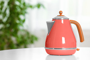 Stylish electrical kettle on table against blurred room interior. Space for text