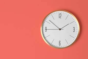 Stylish analog clock hanging on light wall. Space for text