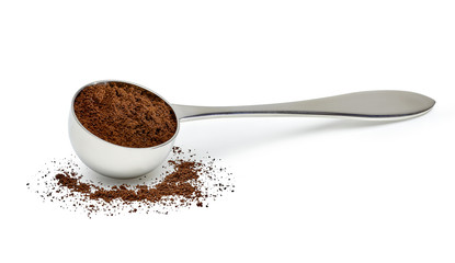 Grinded coffee powder in measuring scoop with beans isolated on white background