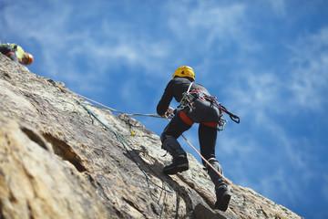 Foto op Aluminium Alpinisme Climber climbs on the rock wall against a blue sky. Climbing gear. Climbing equipment.