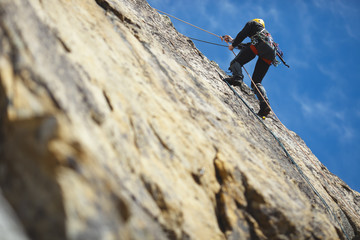 Climber climbs on the rock wall against a blue sky. Climbing gear. Climbing equipment.