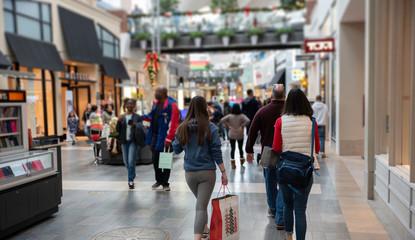 Shoppers walk through a crowded mall a few days before Christmas