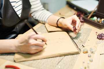 Close up of unrecognizable woman drawing sketches while creating beautiful handmade jewelry, copy space