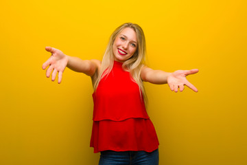 Young girl with red dress over yellow wall presenting and inviting to come with hand