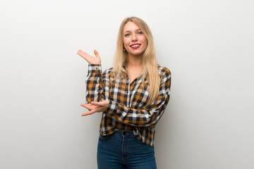 Blonde young girl over white wall extending hands to the side for inviting to come