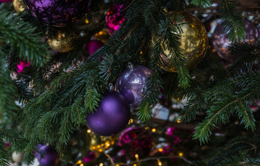 Christmas tree closeup. Red and golden balls and illuminated garland with flashlights.