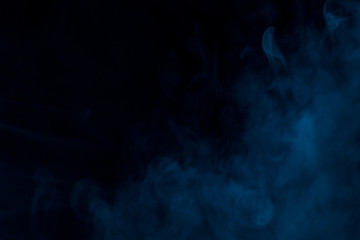 mysterious blue smoke thick and charming on a dark background