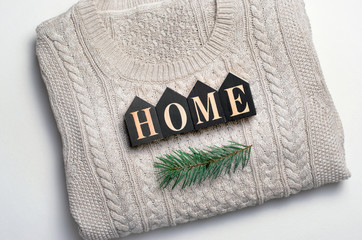 Cozy Winter Concept, Home Letters on Beige Knitted Sweater and Fir Branch, Top View