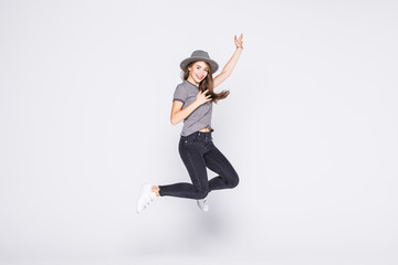 Attractive beautiful young girl wearing casual flying in air isolated over grey background