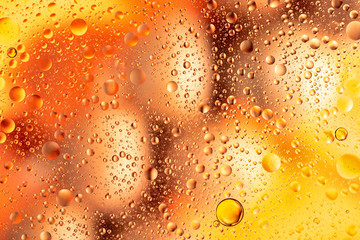 water drops on glass with orange and pink background, close-up