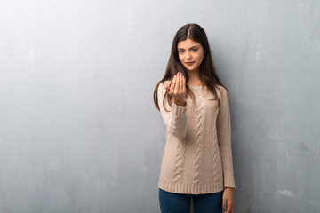 Teenager girl with sweater on a vintage wall inviting to come with hand. Happy that you came