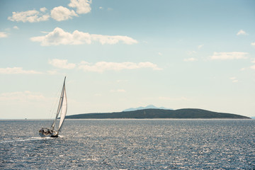 A sail boat cruising near islands in the Adriatic Sea and the Dalmatian Coast of Croatia.
