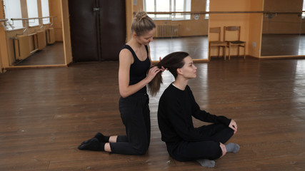 Two female blonde and brunette ballet dancers wearing tights stretching in a studio and one tying the others hair into a low pony tail
