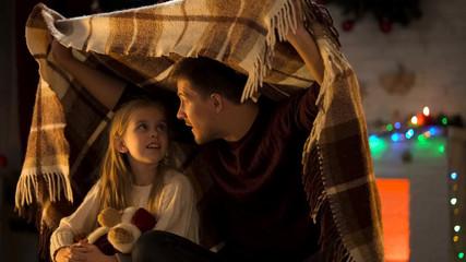 Father telling breathtaking X-mas story for little girl sitting under cozy plaid