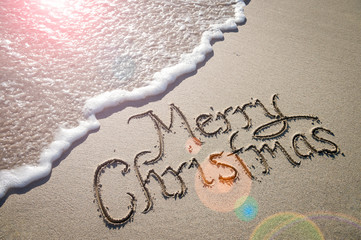 Merry Christmas message handwritten in smooth sand with an oncoming wave in the lens flare of the tropical sun