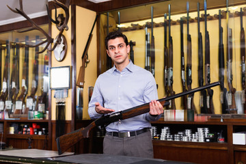 Handsome adult male owner of hunting shop offering rifle
