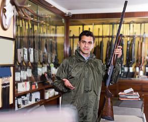 Young male hunter choosing shotgun in store
