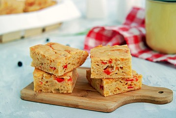 Slices of traditional American corn bread with cheddar cheese and sweet peppers on a gray background.