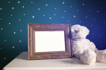 picture frame and white teddy bear in kids room