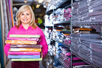 Portrait of mature woman showing stack of bedsheet in the textile shop