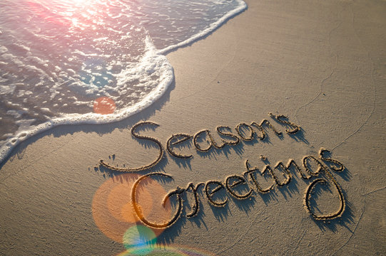 Season's Greetings message handwritten in smooth sand with an oncoming wave in the lens flare of the tropical sun