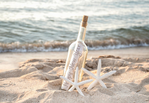Happy New Year message in a bottle with pair of white starfish in beach sand and ocean water background