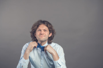 Studio shot of young male hipster adjusting his bow-tie in mirror isolated on grey background. Dark curly hair groom in blue shirt preparing for meeting with the bride. Looking at camera and smiling