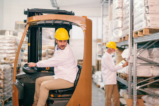 Young warehouse worker driving forklift. In background senior worker with helmet on head checking temperature in warehouse.