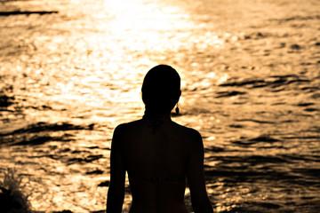 Silhueta de mulher em praia dourada