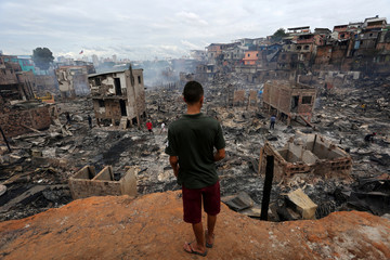 Resident is seen after a fire at Educandos neighbourhood, on a branch of the Rio Negro, a tributary to the Amazon river, in the city of Manaus