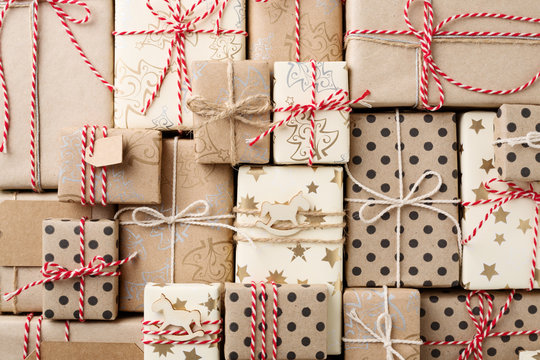 Christmas background with many decorative homemade gift boxes wrapped in brown kraft paper. Flat lay.