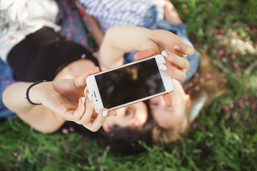 Young beautiful mother  and her little daughter making selfie at mobile phone. Mum and her baby girl outdoors having fun in the park. Girls making picture at cell phone and smiling