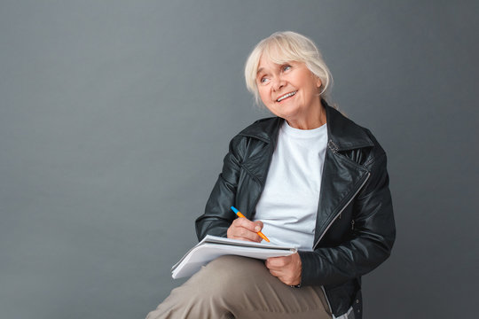 Senior woman writer in leather jacket studio sitting isolated on gray taking notes ideas for story smiling dreamful