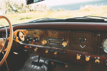 Color image of the dashboard of a retro car inside.