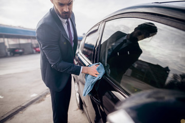 Businessman polishing his car with microfiber cloth in front of car wash..