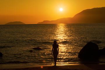 Silhueta de mulher durante o pôr do sol na praia