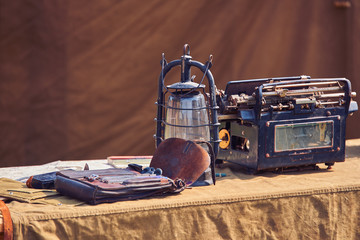Vintage lantern and old typewriter on military table