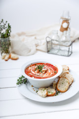 Tomato soup on white with cream and herbs. Top view, copy space