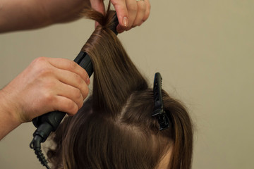 Hairdresser working at the beauty studio salon, making hair style.